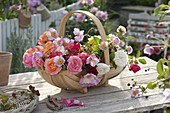 Woodchip basket with freshly cut roses and anemone hupehensis