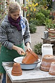 Woman cleans clay pots