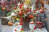 Autumn bouquet with physalis, miscanthus, cotoneaster