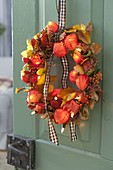 Door wreath made of physalis, pyracantha, leaves