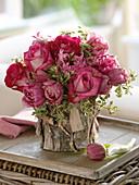 Rosaroter Frühlingsstrauß in mit Rinde verkleideter Vase
