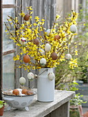 Easter bouquet of forsythia (gold bells) with painted easter eggs