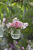 Small glass with Lathyrus and Rose hanged on branch