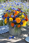 Tying blue-orange summer flower bouquet