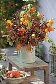 Autumn bouquet of wild fruits and physalis, roses
