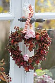 Heart made of roses (rosehip) and rose blossom with moss on the window
