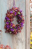 Autumn wreath with violet cushions and red foliage