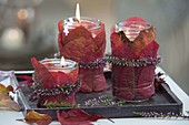 Jam jars with red autumn leaves wrapped as lanterns