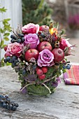 Autumnal bouquet with rose, apples and ornamental apples