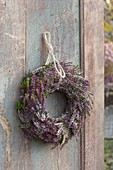 Kranz aus Calluna vulgaris (Knospenbluehender Besenheide) an alter Holztuere