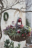 Christmas decorated wicker basket with Santa Claus and red balls
