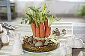 Easter basket with carrots and eggs, ceramic bunnies