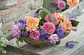Woodchip basket with different roses and geranium