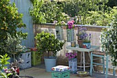 Greek-Mediterranean balcony with planters and stools
