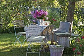 Table laid under apple tree with bouquet of summer flowers