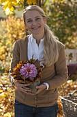 Frau mit Herbstgesteck aus Dahlia (Dahlie) und Blättern von Acer (Ahorn)