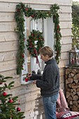 Decorate window with garland and wreath for Christmas