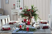 Christmas table decoration with bouquet of Ilex, Pinus