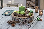 Advent decoration with green candle, balls and cones in wooden bowl