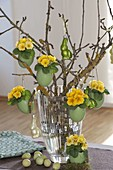 Easter bouquet of twigs, green colored duck eggs planted with primula