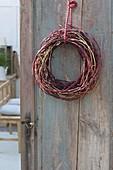 Wreath of different-colored branches of cornus on door