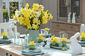 Easter table decoration with narcissus and easter bunny
