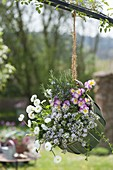 Green basket hanging by the handle on blooming thyme