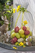 Colorful easter eggs under hood made of chicken wire with viola cornuta flowers