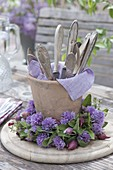 Terracotta vase with cutlery in chives flowers wreath