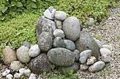 Pebbles stacked on flower bed as a stone sculpture