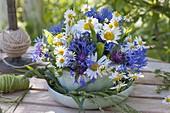 Blue-white mini jar in cup with saucer Centaurea montana