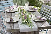 Early summer table decoration grass plait as table garland decorated with camomile