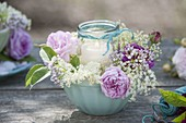 Glass as a lantern in cereal bowl with rose and elder flowers