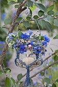 Preserving jar with macrame as lantern on tree, small summer wreath