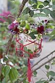 Preserving jar with macrame as lantern on tree, wreath of tropaeolum