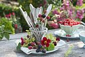 Preserving jar with cutlery in wreath of blackberries (Rubus), fennel