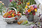 Woodchip basket with freshly picked tomatoes, small bouquet