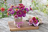 Small zinnia (zinnia) and grasses bouquets in tin can