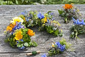 Blue-yellow-orange wreath of edible flowers and herbs