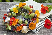Small edible flowers wreath, tea herbs and wild fruits