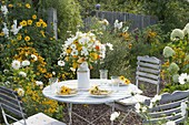 Small seating place at the yellow and white bed with Dahlia 'My Love'