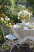 Small seat at the yellow and white bed with Dahlia 'My Love'