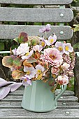 Pink autumn bouquet on garden chair Zinnia, rose, anemone