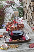 Bottle of red wine liqueur as a gift with a rosehips bouquet