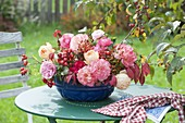 Arrangement in old cake form with rose (rosehips) on garden table
