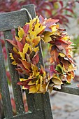 Yellow and red autumn leaves wreath hanged on bench