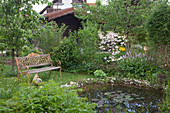 Romantic spring garden with bench at the pond