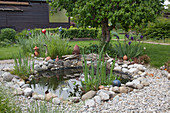 Small foil pond with natural stones bordered in the garden