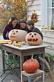 Family carving pumpkins for Halloween