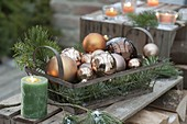Metal basket with branches of pinus, abies and copper colored balls